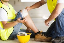 construction worker with broken leg being assisted by co-worker