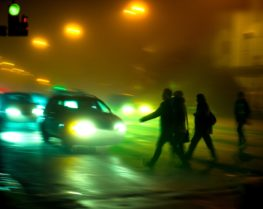 Pedestrians about to be hit by a car in the dark