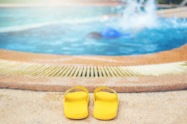 pair of yellow flip flops poolside with drowning child in water