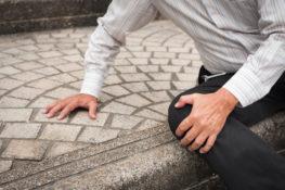 senior man grabbing knee after falling