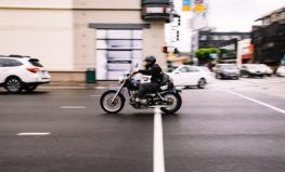 Male driving a motorcycle through a city