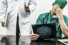Surgical doctor covering his face with hand (face palm) expressing disappointment while holding xray film on office desk