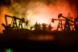 Oil war concept. Military silhouettes at oilfield with pumps and rigs. Misty colorful sky background. Armored vehicles fighting scene. Selective focus