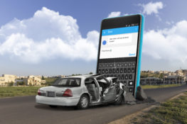 graphic of gray car wrecked front end by oversized smartphone in road