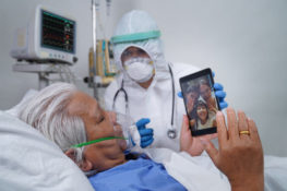 elder covid-19 patient talking with family remotely