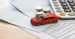 toy car beside money and papers representing car insurance